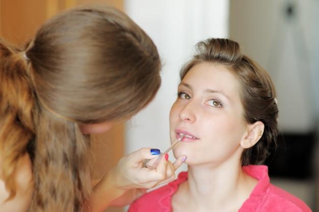 Jeune belle mariée appliquant le maquillage de mariage par maquilleuse professionnelle Photo Premium