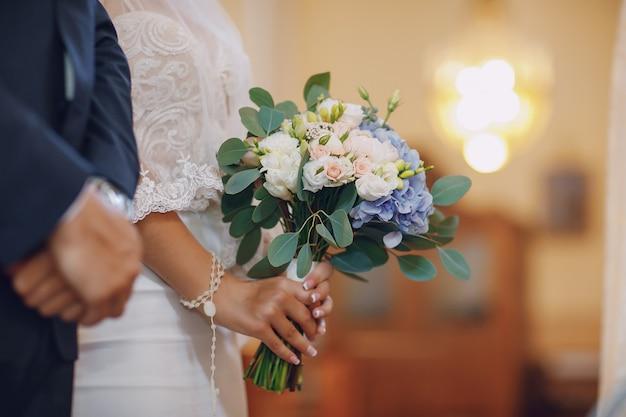 Une jeune et belle mariée est debout avec son mari dans une église Photo gratuit