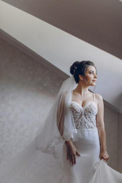 Une jeune et belle mariée à la maison debout près de la fenêtre Photo gratuit