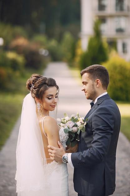 Une jeune et belle mariée et son mari debout dans le parc avec bouquet de fleurs Photo gratuit