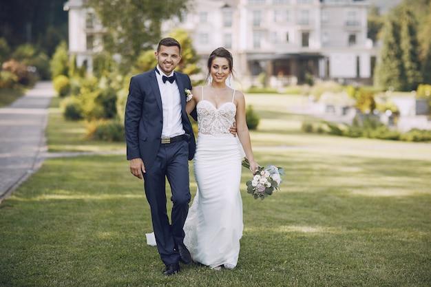 Une jeune et belle mariée et son mari debout dans un parc d'été avec bouquet Photo gratuit