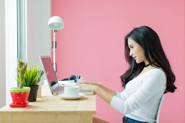 Jeune belle travaillant au bureau de l'ordinateur Photo gratuit