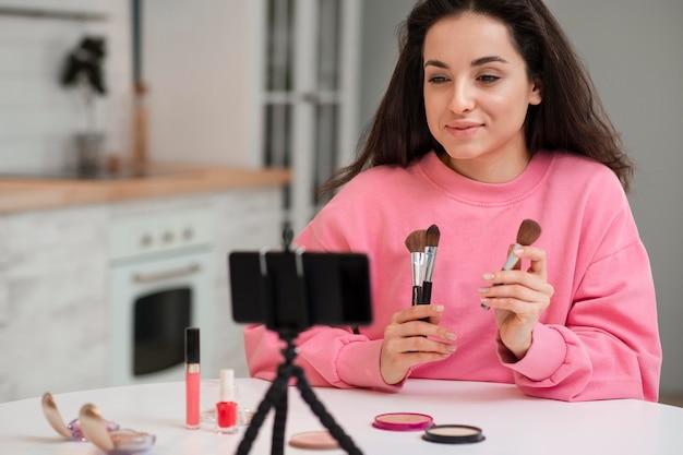 Jeune Blogueuse Enregistrant Une Vidéo Avec Des Accessoires De Maquillage Photo gratuit
