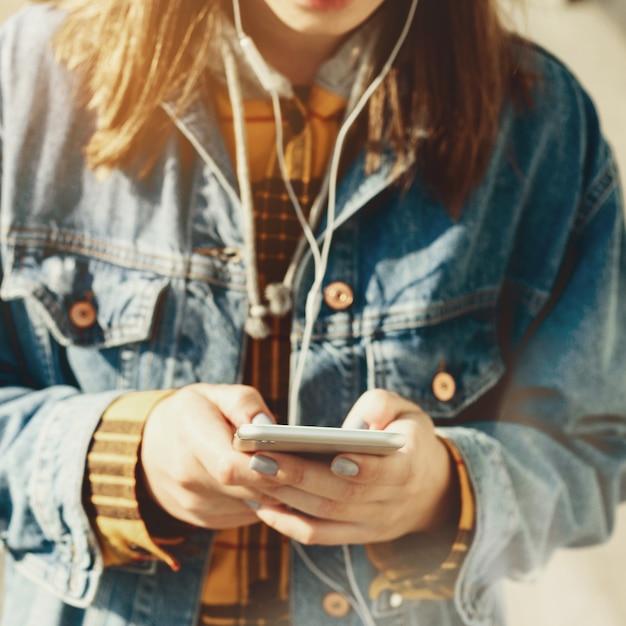 Jeune blogueuse parcourant les réseaux sociaux dans la rue. femme sms sur son téléphone Photo Premium