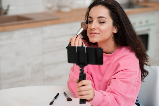 Une Jeune Blogueuse S'enregistre Et Se Maquille Photo gratuit