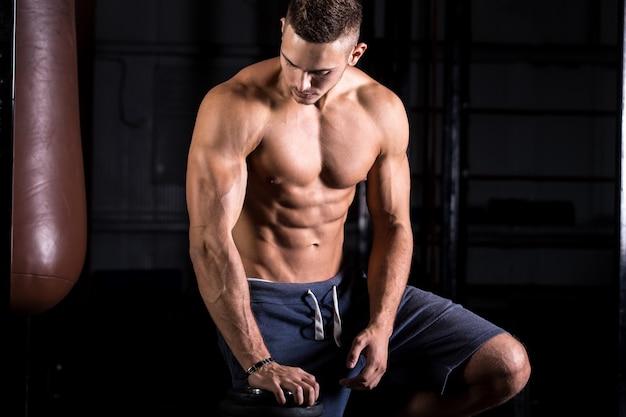Jeune Bodybuilder Avec Corps Parfait Photo gratuit