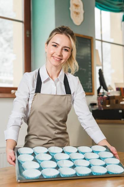 Jeune boulanger montrant une plaque de cuisson remplie d'un étui vide de cupcakes bleus Photo gratuit