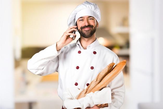 Le jeune boulanger prend du pain et parle au mobile dans la cuisine Photo Premium