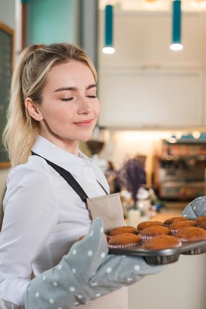 Jeune Boulangère Profitant De L'odeur Agréable Des Muffins Au Four Photo gratuit