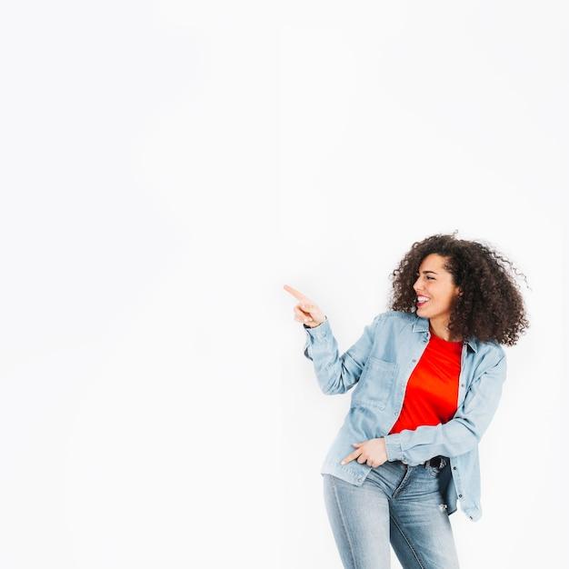 Jeune Brune Dansant Et Pointant à Gauche Photo gratuit