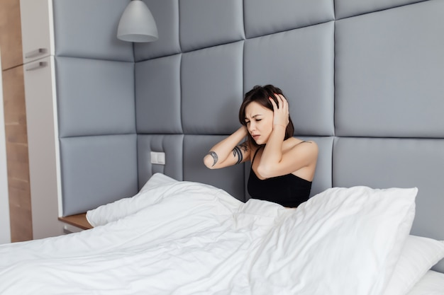 Jeune Brune Montre Un Regard Malsain Le Matin Après Avoir Dormi Dans Son Grand Lit Photo gratuit