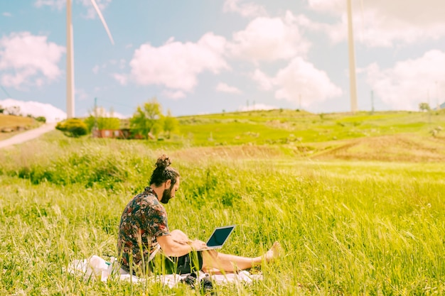 Jeune brunet assis avec un ordinateur portable en milieu rural Photo gratuit