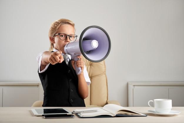 Jeune, caucasien, garçon, debout, à, bureau exécutif, dans, bureau, à, haut parleur, et, pointage doigt Photo gratuit