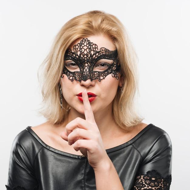 Jeune charmante femme blonde en masque avec un doigt près des lèvres Photo gratuit