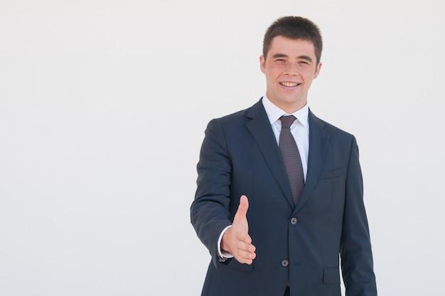 Jeune chef d'entreprise prospère offrant la main à une poignée de main Photo gratuit