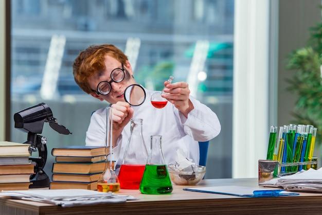 Jeune chimiste fou travaillant dans le laboratoire Photo Premium