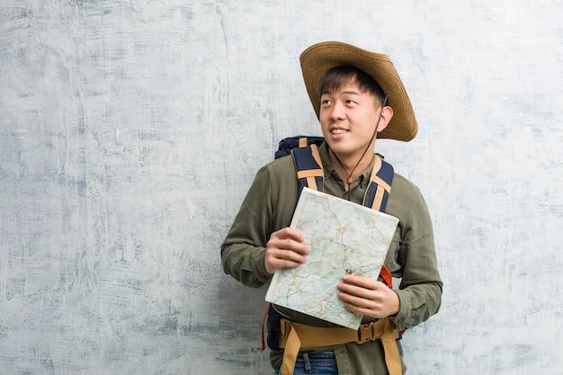Jeune, Chinois, Explorateur, Homme, Tenue, Carte, Sourire, Confiant, Croisement, Bras, Levant Photo Premium