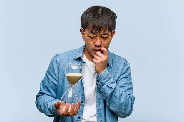Jeune, chinois, tenue, sablier, relax, penser, quelque chose, à, a Photo Premium