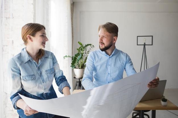 Jeune collègue masculin et féminin se regardant tout en maintenant le plan d'action au bureau Photo gratuit