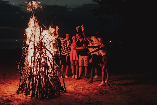 Jeune compagnie dansant autour du feu de joie sur la plage. Photo Premium