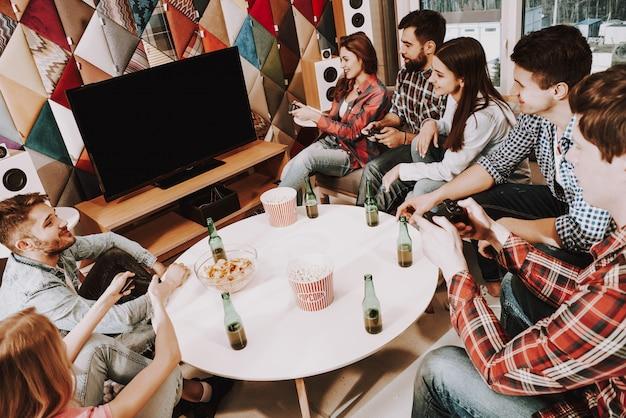 Jeune compagnie jouant à des jeux vidéo sur une fête Photo Premium