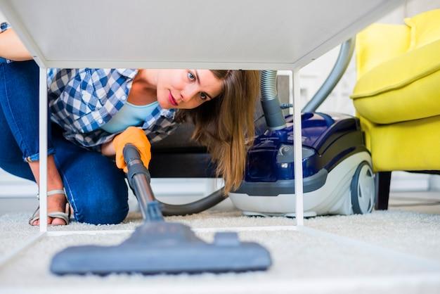 Jeune concierge nettoyant tapis avec aspirateur Photo gratuit