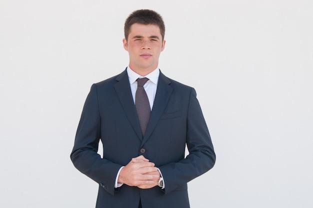 Jeune consultant songeur debout devant la caméra Photo gratuit
