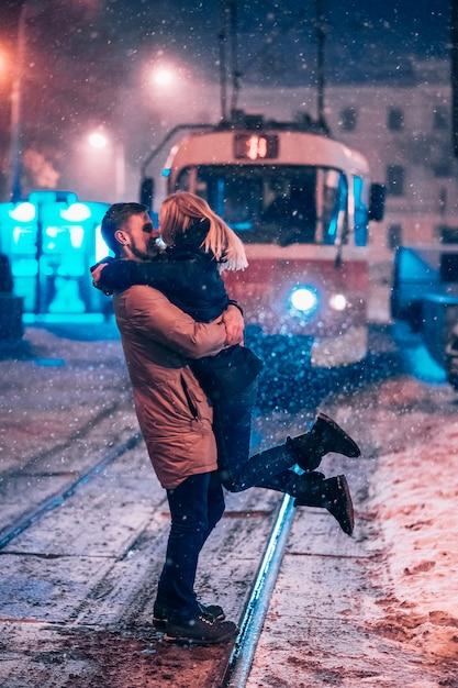 Jeune couple adulte sur la ligne de tram enneigée Photo gratuit
