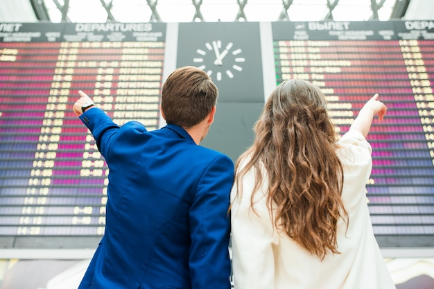 Jeune couple à l'aéroport international en regardant le panneau d'information de vol Photo Premium