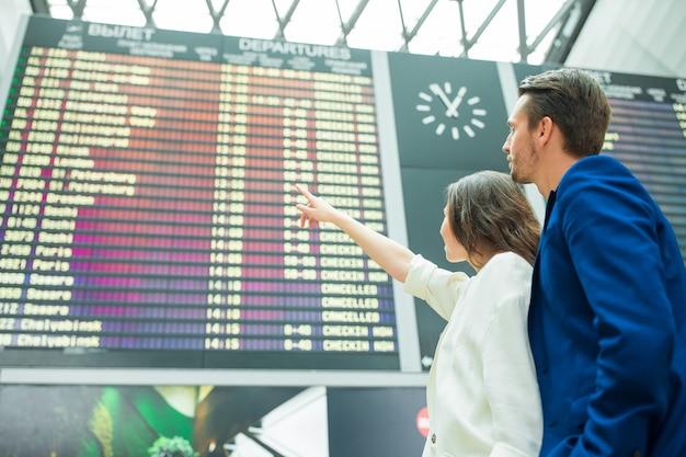 Jeune couple à l'aéroport international en regardant le panneau d'information de vol Photo Premium