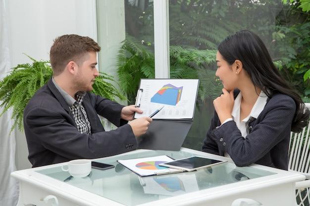 Le jeune couple d'affaires prospère parle et regarde des documents Photo Premium
