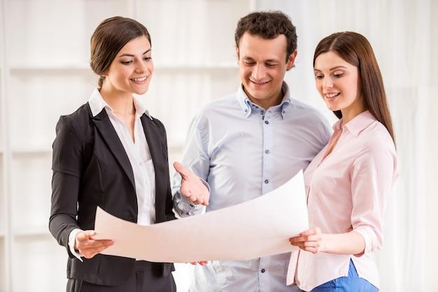 Jeune couple avec agent immobilier surveille le plan d'une maison. Photo Premium