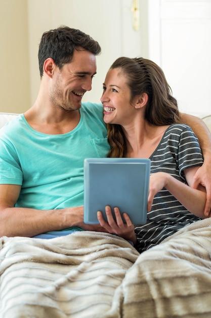 Jeune couple à l'aide de tablette numérique sur un canapé à la maison Photo Premium