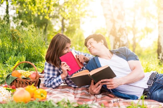 Jeune couple allongé sur une couverture et lire des livres Photo gratuit