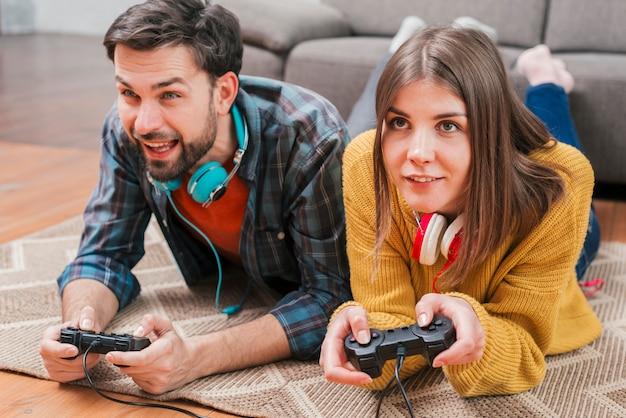 Jeune couple allongé sur un tapis jouant au jeu vidéo Photo gratuit