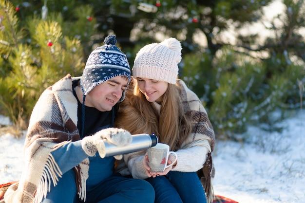Jeune couple amoureux boire une boisson chaude d'un thermos, assis en hiver dans la forêt Photo Premium