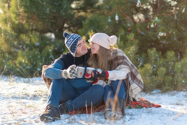 Un jeune couple amoureux boit une boisson chaude avec des guimauves, assis en hiver dans la forêt, niché dans des tapis chauds et confortables et profite de la nature. ils parlent et rient pour une tasse de boisson chaude en forêt Photo Premium