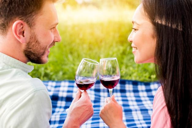 Jeune couple amoureux multiethnique, boire du vin rouge sur pique-nique Photo gratuit