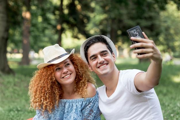 Jeune couple d'amoureux en plein air prenant un selfie Photo gratuit