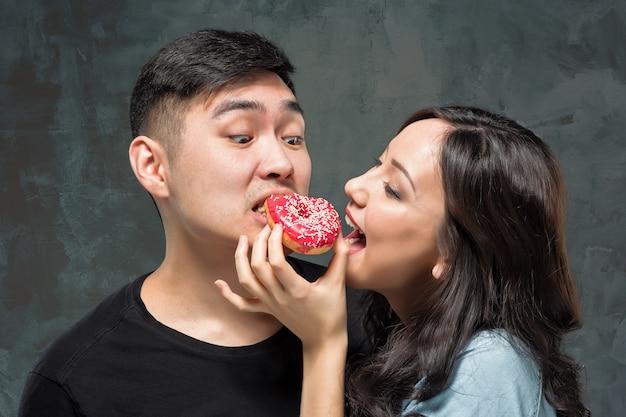 Jeune Couple Asiatique Aime Manger Un Beignet Coloré Sucré Photo gratuit