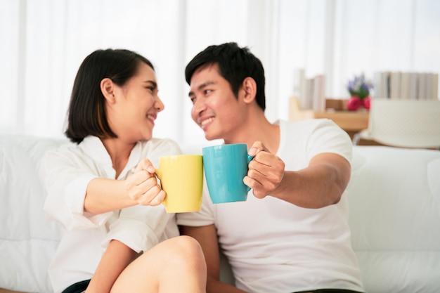 Jeune Couple Asiatique Appréciant Avec Café Le Matin Dans La Mauvaise Chambre, Les Loisirs, Le Couple, La Relation Et La Saint-valentin. Photographie Avec Fond. Photo Premium
