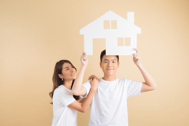Jeune couple asiatique heureux présentant les symboles de la maison Photo gratuit