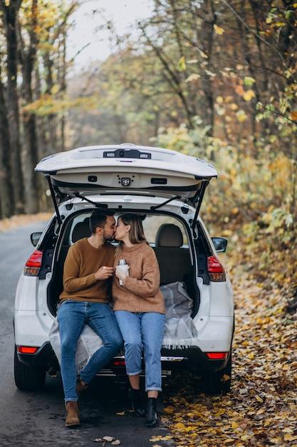 Jeune couple assis à l'arrière d'une voiture, buvant du thé en forêt Photo gratuit
