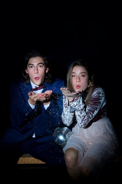 Jeune couple assis sur un banc et souffle un baiser Photo gratuit