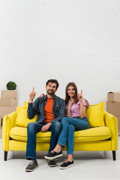 Jeune couple assis sur un canapé jaune pointant leurs doigts vers le haut et regardant vers la caméra Photo gratuit