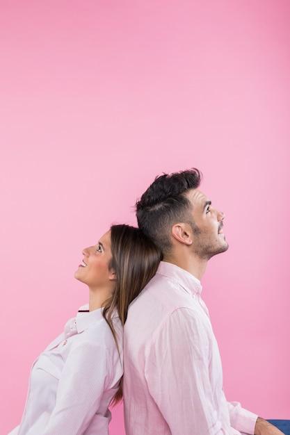 Jeune couple assis dos à dos Photo gratuit