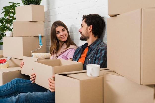 Jeune couple assis entre les cartons se regardant Photo gratuit