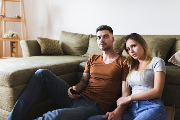Jeune couple assis près du canapé en regardant la télévision à la maison Photo gratuit