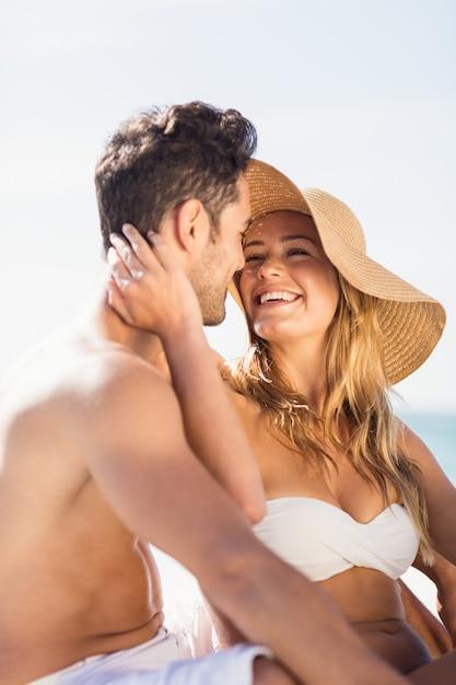 Jeune couple assis sur le sable Photo Premium