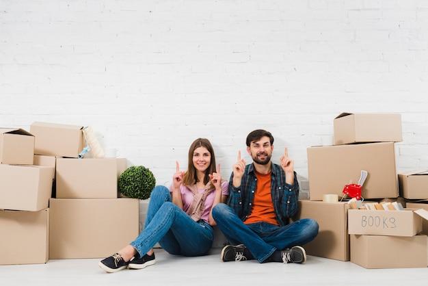 Jeune couple assis sur le sol, tenant leurs doigts vers le haut, assis entre les boîtes en carton Photo gratuit